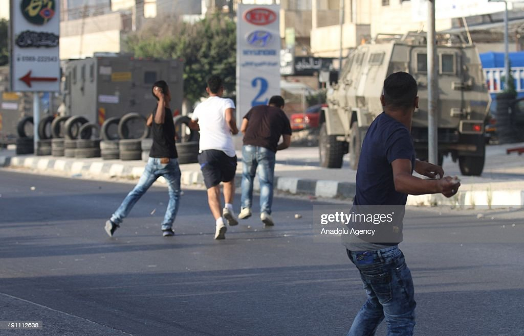 Palestinians throw stones at an Israeli military vehicle during the clashes with Israeli soldiers in the West Bank city of Nablus as they search for...