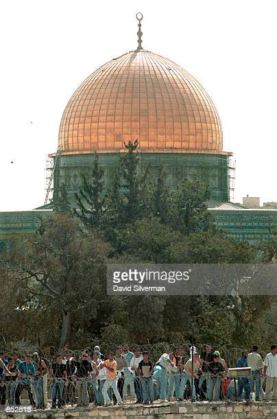 Palestinians throw stones at Israeli police from the walls of the Temple Mount near the golden Dome of the Rock rear and alAqsa Mosque October 6 2000...
