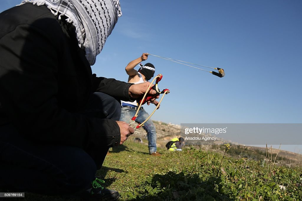 Palestinians throw stones at Israeli soldiers during a protest against Israel's practices, its settlement policies, its decision on administrative detention and the continuing detention of journalist Mohammed al-Kayak who has been on hunger strike for 80 days against arbitrary measures, in front of Ofer prison in the west of the city of Ramallah on the West Bank on February 12, 2016. Palestinians threw back tear gas capsules used in an intervention by the Israeli security forces.