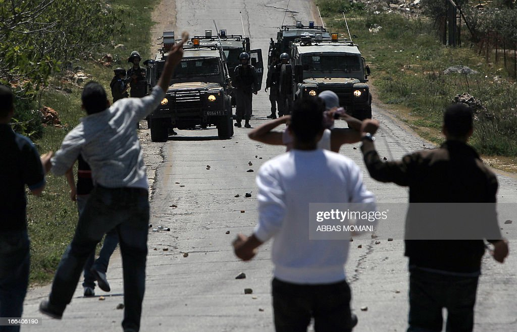 Palestinians throw stones towards Israeli security forces during clashes following a protest against the expropriation of Palestinian land by Israel in the West Bank village of Silwad, east of Ramallah, on April 12, 2013.