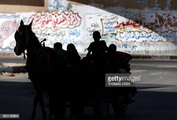 Palestinians travel back to their home after they left the north of the Gaza strip to seek refuge at an UNRWA school due to Israeli air strikes on...