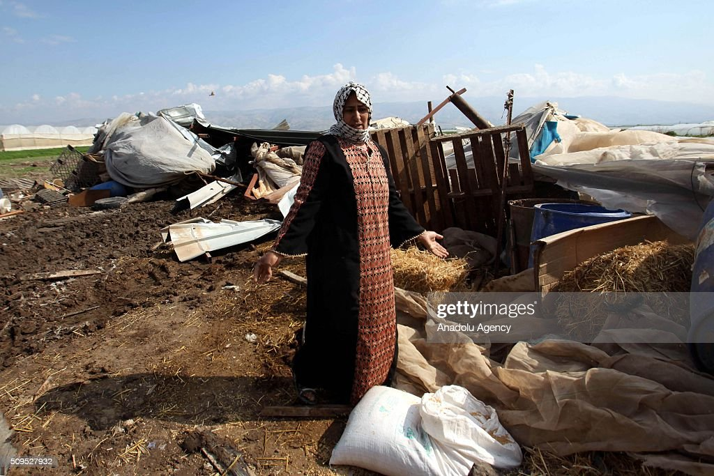 Palestinians try to collect their useable household goods and belongings inside the debris after Israeli authorities demolished theirs huts and tents, in Al-Agvar region of West Bank's Jericho on February 11, 2016.