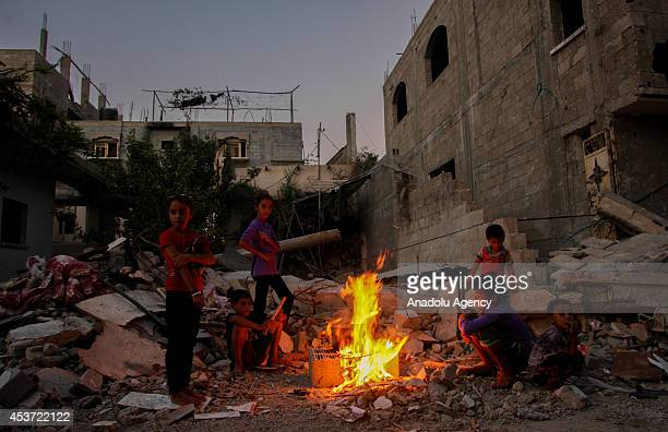 Palestinians try to hold on life amid the debris of buildings destroyed in Israeli attacks on August 16 2014 in the northeast city Beit Hanoun Gaza...