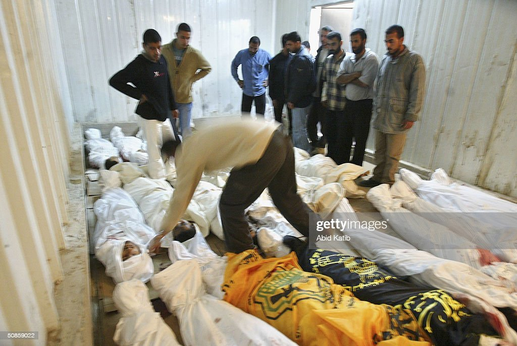 Palestinians try to recognise their relatives amongst 29 bodies, killed by Israeli attacks, stored in a vegetables and flowers freezer being used as a makeshift morgue, on May 20, 2004 in the Rafah refugee camp, southern Gaza Strip. Israel defied international fury at the killing of nearly 40 Palestinians in the Rafah refugee camp, to expand its bloodiest Gaza Strip raid in years on Thursday.
