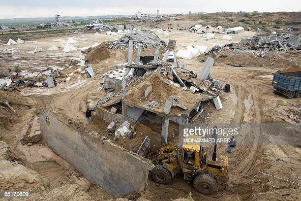 Palestinians use a bulldozer to remove debris of a house which was destroyed during Israel's 22day offensive in Jabalia in the northern Gaza Strip on...