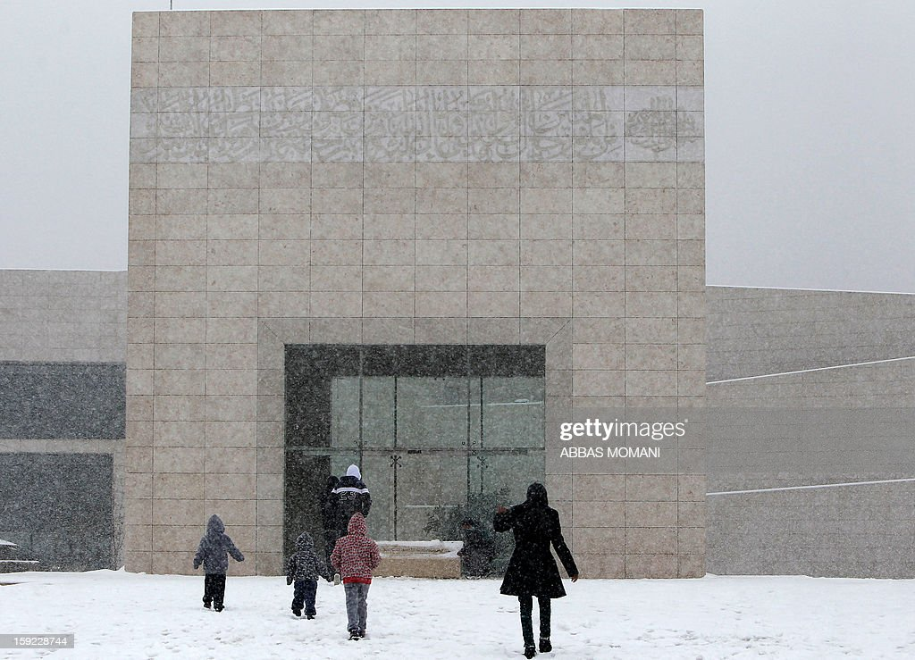 Palestinians visit late Palestinian leader Yasser Arafat's mausoleum as snow falls in the West Bank city of Ramallah on January 10, 2013. Abnormal storms which have blasted the Middle East with rain, snow and hail have claimed at least 11 lives in a region accustomed to temperate climates.