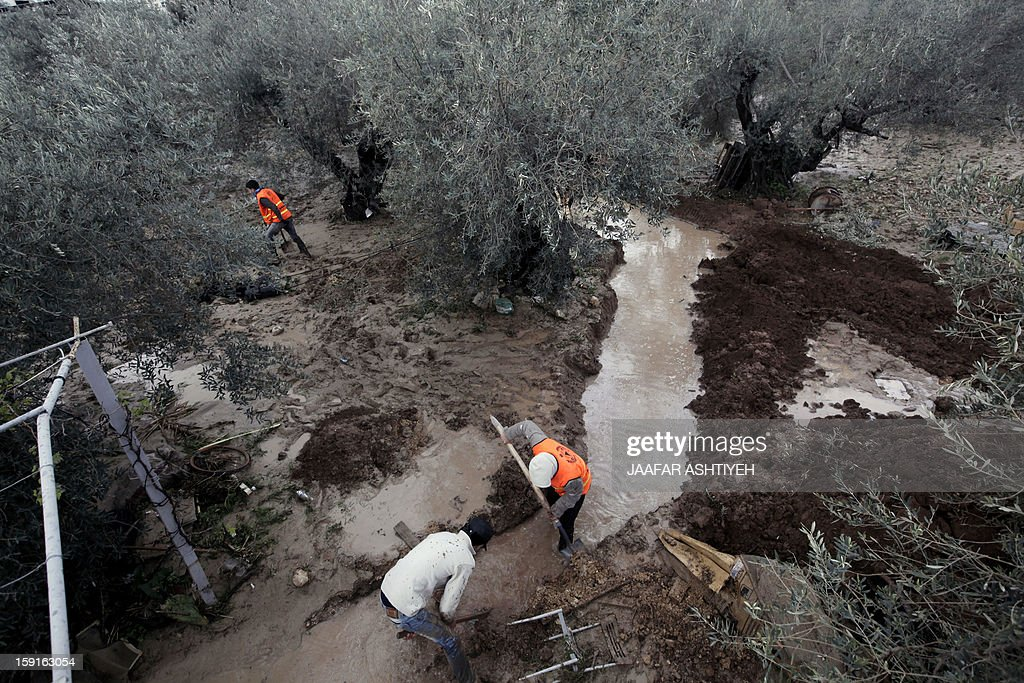 Palestinians volunteers and civil defense workers search in area where two girls drowned following flooding in the West Bank city of Tulkarem on January 9, 2013. Two women were declared dead after flooding in the northern West Bank swept their car away, as a fierce storm whipped the region, and forecasters predicted snow as temperatures dropped.