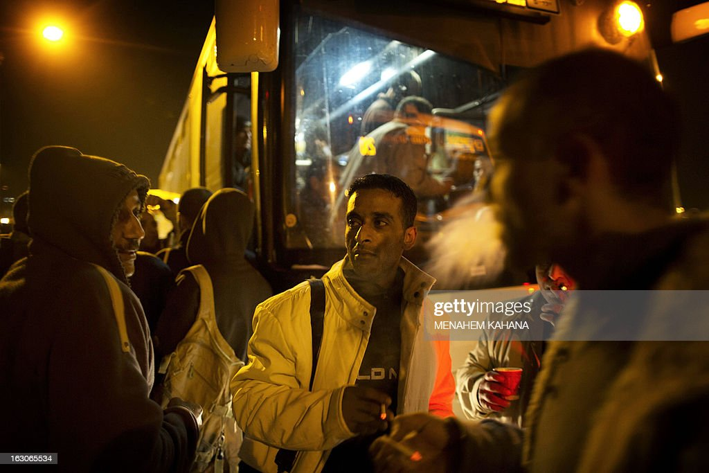 Palestinians wait before boarding a bus as a new line is made available by Israel to take Palestinian labourers from the Israeli army crossing Eyal, near the West Bank town of Qalqilya, into the Israeli city Tel Aviv, on March 4, 2013.Thousands of Palestinians enter Israel to work every day after receiving permits, many of them in private vans. The new line will not be available for Jewish settlers.