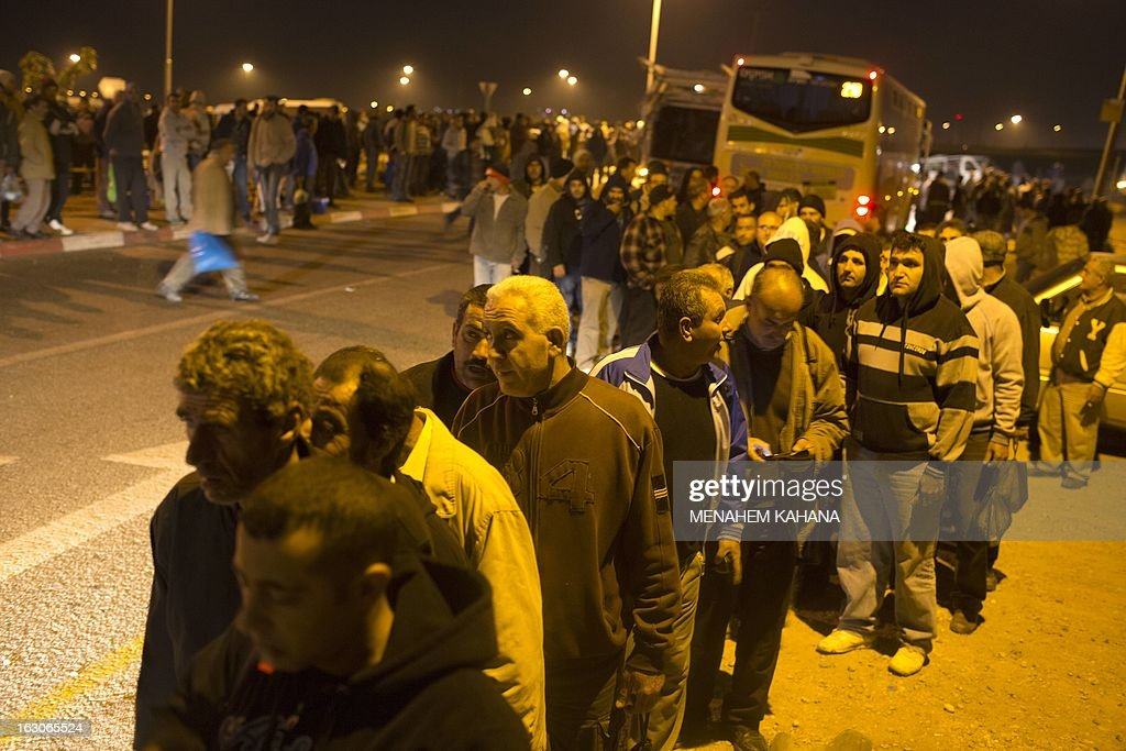 Palestinians wait before boarding buses as a new line is made available by Israel to take Palestinian labourers from the Israeli army crossing Eyal, near the West Bank town of Qalqilya, into the Israeli city Tel Aviv, on March 4, 2013.Thousands of Palestinians enter Israel to work every day after receiving permits, many of them in private vans. The new line will not be available for Jewish settlers. AFP PHOTO / MENAHEM KAHANA