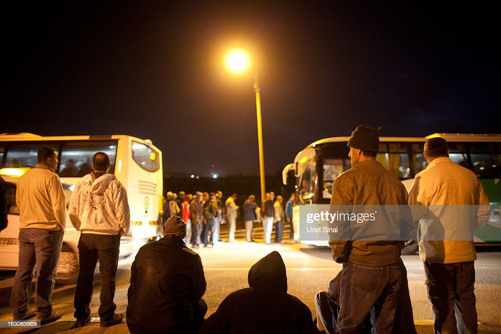 Palestinians wait to board a bus as a new line is made available by Israel to take Palestinian labourers from the Israeli army crossing of Eyal, near the West Bank town of Qalqilya, into the Israeli cities, on March 4, 2013. at Eyal crossing, West Bank.The new line service to ferry Palestinian workers from the West Bank to Israel, encouraging them to use it instead of traveling with Israeli settlers on a similar route.
