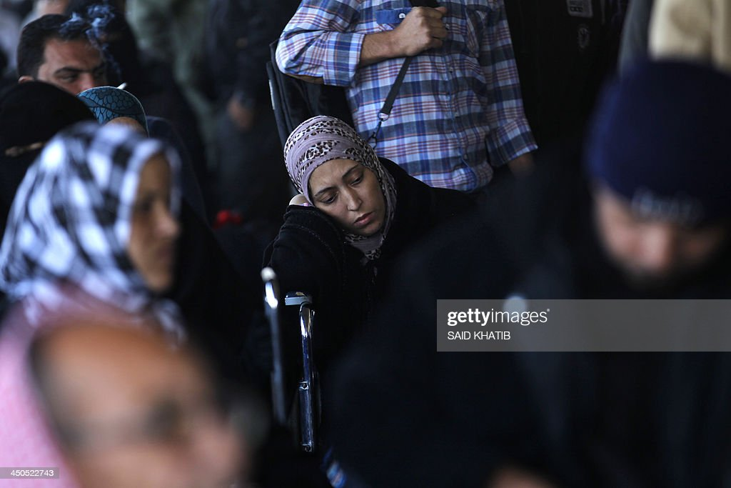 Palestinians wait to cross from the Gaza Strip to Egypt at the Rafah crossing terminal on November 19, 2013. Hundreds of patients, students and foreign residents from the Palestinian side have rushed to the Rafah crossing after the Egyptian announcement of re-opening it for 3 days. AFP PHOTO / SAID KHATIB