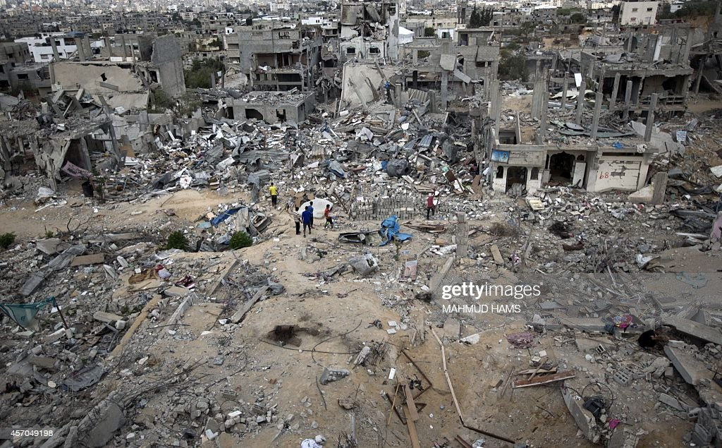 Palestinians walk amidst destroyed buildings in alTufah east of Gaza City on October 11 ahead of a donors conference in Cairo aimed at gathering...