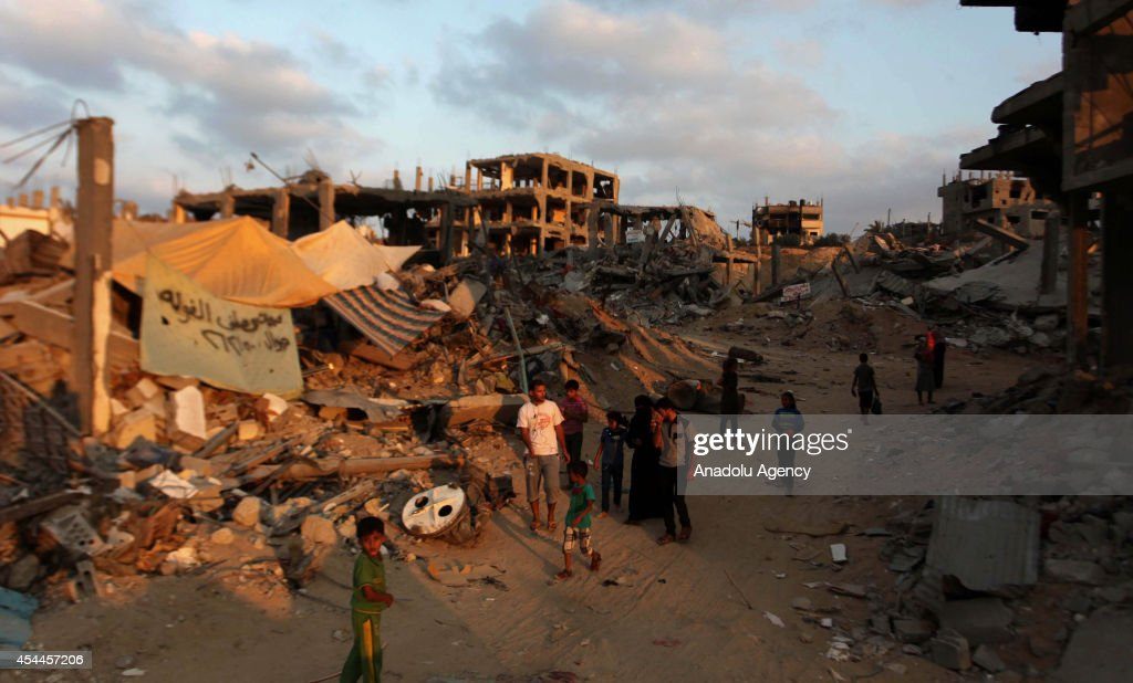 Palestinians walk among the debris of destroyed buildings as they start to return their homes during ceasefire in al-Shaaf neighborhood Gaza City, Gaza on August 31, 2014.