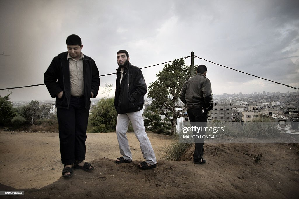 Palestinians walk by the place where four people were killed by Israeli fire on November 10, in the al-Shejaya neighbourhood of Gaza City on November 11, 2012. Five Gazans were killed and 30 injured by Israeli shelling after militants fired an anti-tank rocket at an Israeli jeep, wounding four soldiers, sources on both sides said.