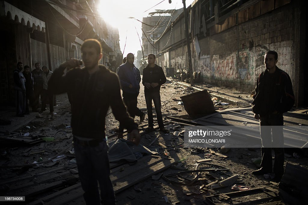 Palestinians walk in a street littered with debris from a house destroyed in an Israeli airstrike on Gaza City, on November 20, 2012. Seven Palestinians were wounded in strikes on Gaza overnight, but no one was killed in the first night without fatalities since the Israeli air campaign began nearly a week ago. AFP PHOTO/MARCO LONGARI