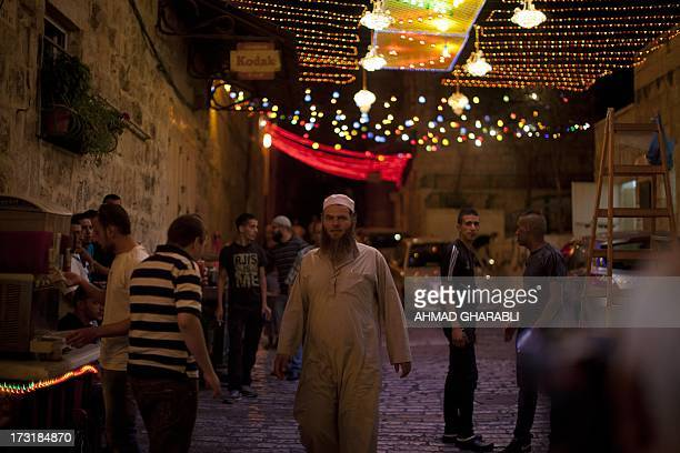 Palestinians walk in an illuminated street before attending the evening prayer at the AlAqsa mosque compound in the old city of Jerusalem during the...