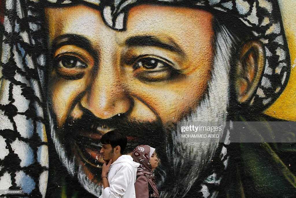 Palestinians walk in front of a mural of late Palestinian leader Yasser Arafat (R) in Gaza City on November 27, 2012. The body of Arafat was exhumed, eight years after his death, as part of an investigation into allegations he was poisoned. AFP PHOTO/MOHAMMED ABED