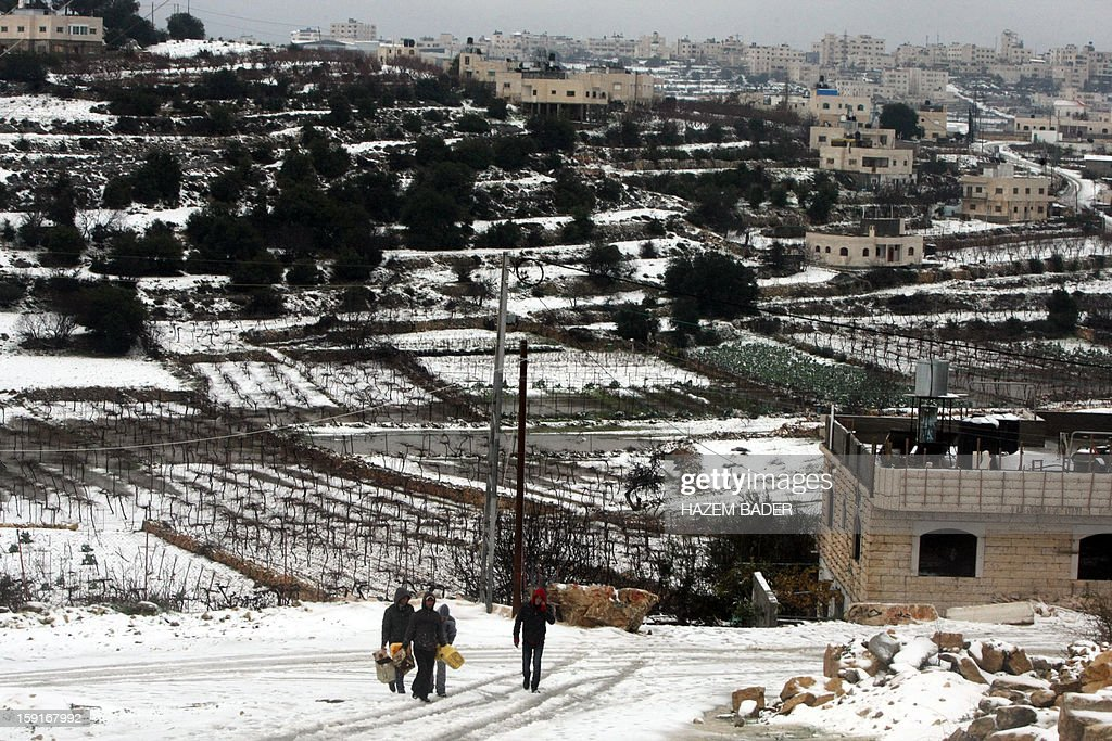 Palestinians walk in the streets in the village of Halhoul, near the West Bank town of Hebron, following the first snow fall of the year on January 9, 2013. Extreme weather, including torrential rains and heavy winds, killed four people in Israel and the Palestinian territories on January 8, as widespread flooding swept the Middle East.
