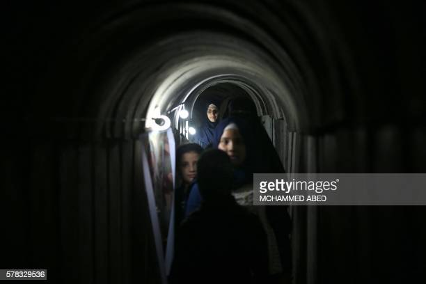 TOPSHOT Palestinians walk inside a tunnel used for military exercises during a weapon exhibition at a Hamasrun youth summer camp in Gaza City on July...