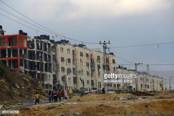 TOPSHOT Palestinians walk near buildings which were destroyed during the 50day war between Israel and Hamas militants in the summer of 2014 in Beit...