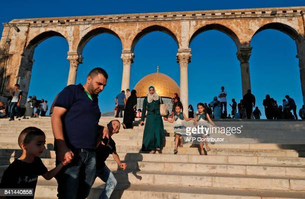 Palestinians walk near the Dome of Rock mosque inside the alAqsa Mosque compound Islam's third holiest site following the morning Eid alAdha prayer...