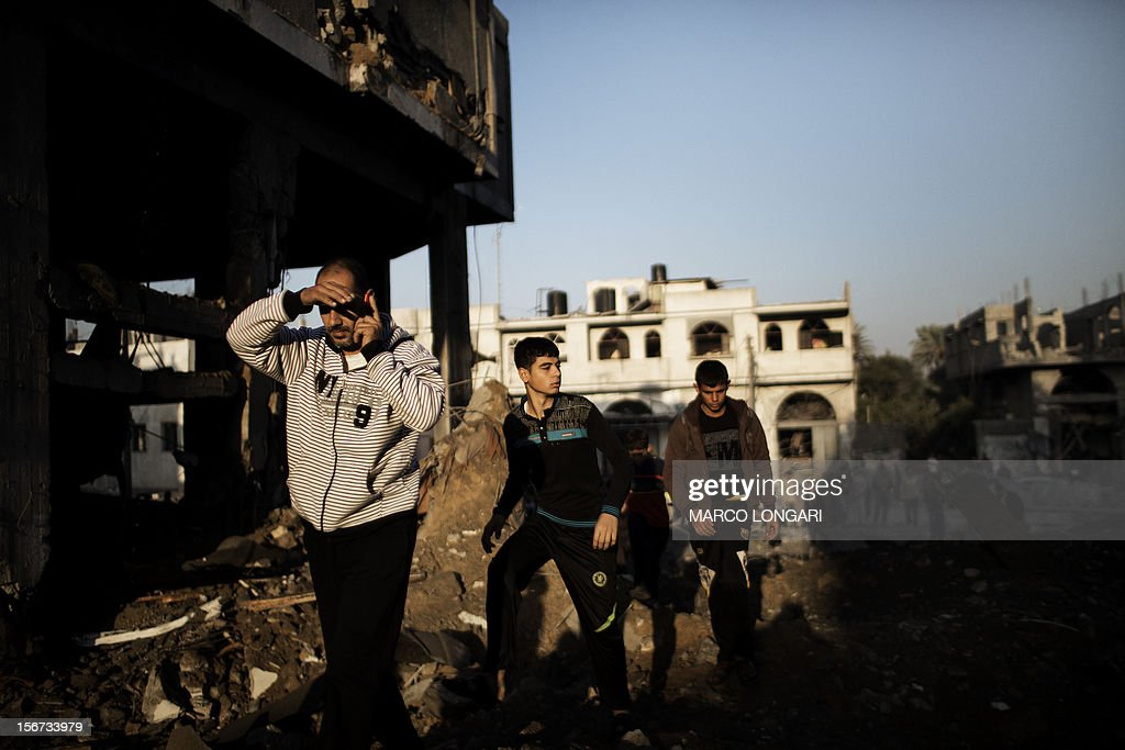 Palestinians walk on the rubble of a house destroyed in an Israeli airstrike on Gaza City, on November 20, 2012. Seven Palestinians were wounded in strikes on Gaza overnight, but no one was killed in the first night without fatalities since the Israeli air campaign began nearly a week ago.