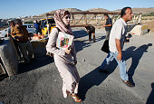Palestinians walk past a barrier blocking access to the alFawwar refugee camp south of the West Bank city of Hebron on July 26 before Israeli...