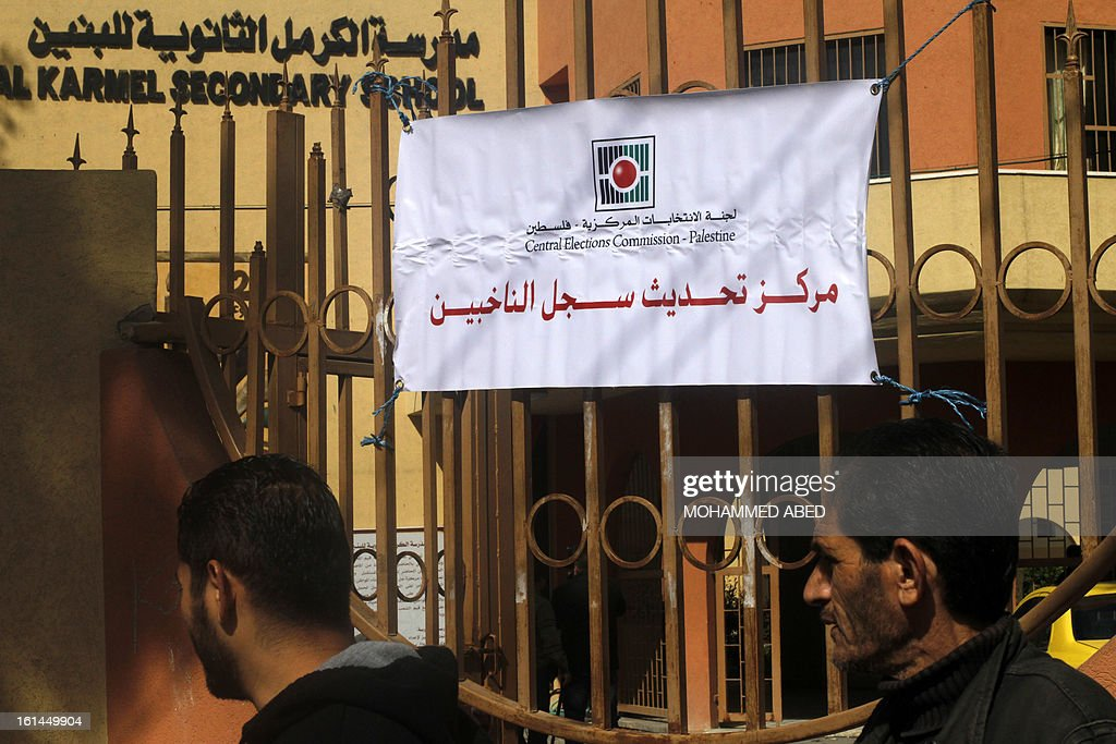 Palestinians walk past a Central Election Commission office in Gaza City on February 11, 2013. Palestinian electoral officials began the long-overdue process of updating voter rolls in the West Bank and Gaza in a vital step towards eventual elections.