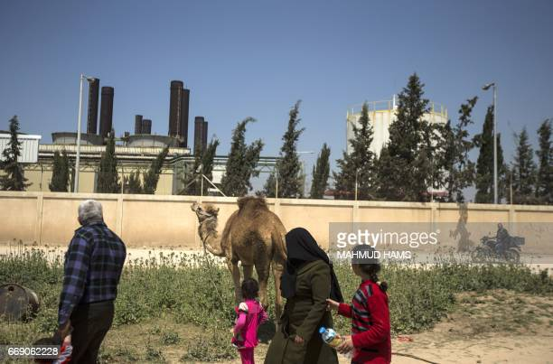Palestinians walk past a power plant in Gaza City on April 16 2017 The Gaza Strip's only functioning power plant was out of action after running out...