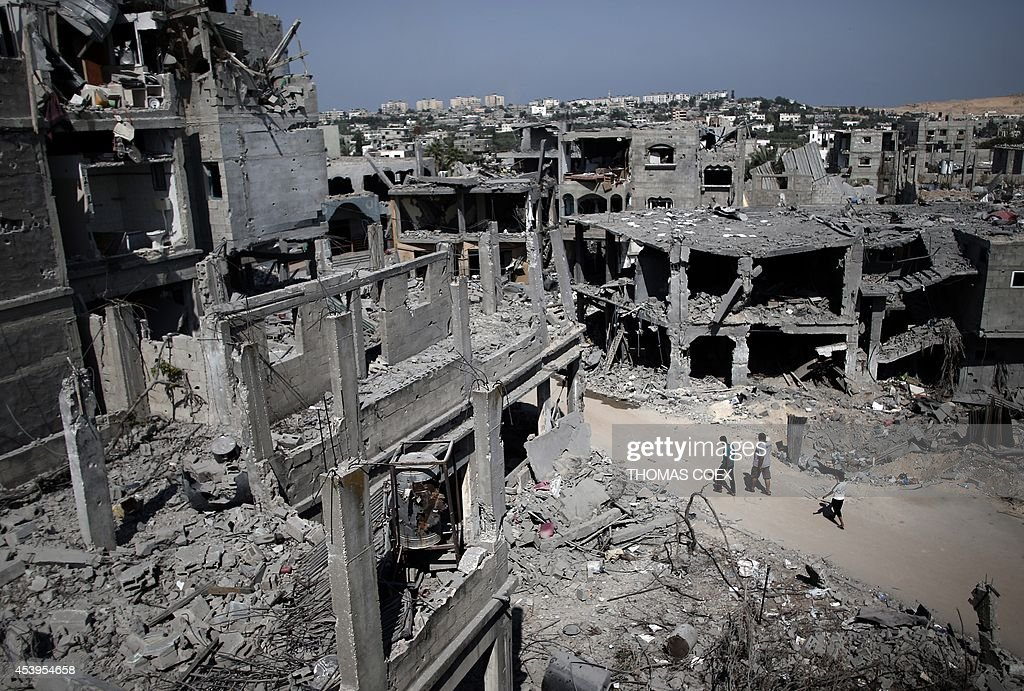Palestinians walk past destroyed buildings in the northern Gaza Strip city of Beit Hanun on August 22, 2014. The Hamas armed wing declared the truce efforts over after Israel carried out an abortive assassination attempt the previous day on its leader Mohammed Deif, killing his wife and two of his children.