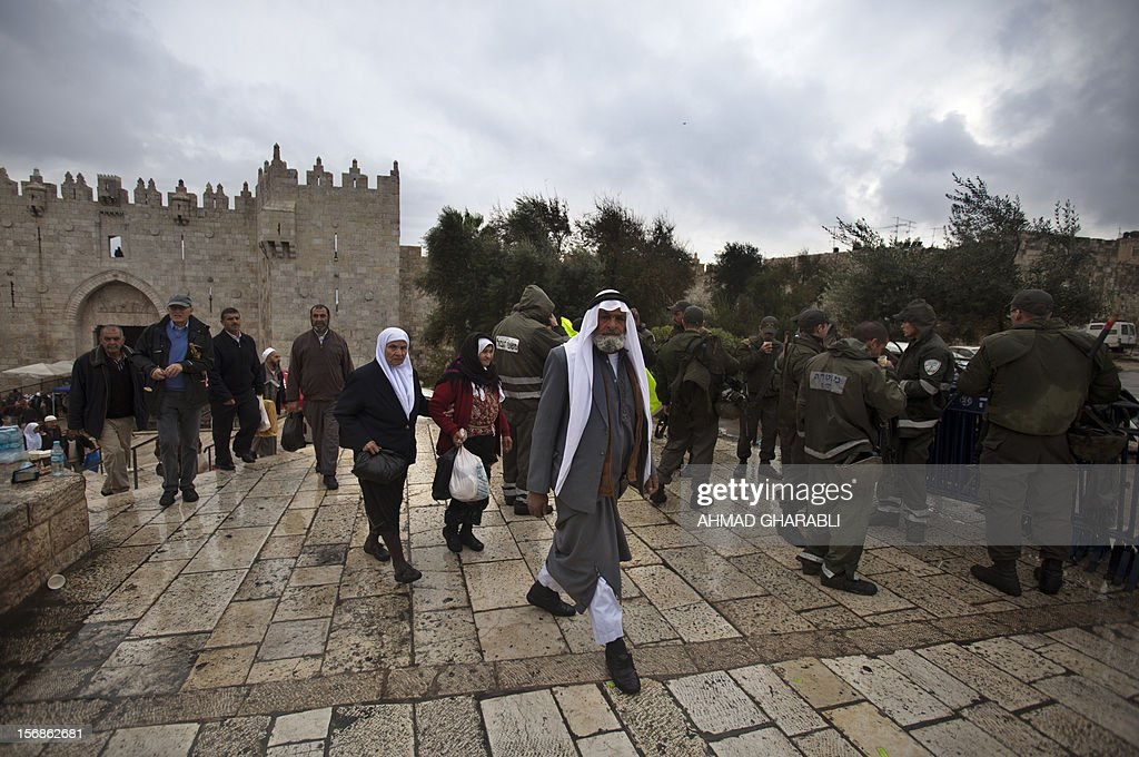 Palestinians walk past Israeli security forces at the entrance of Jerusalem's Old City next to the Damascus Gate on November 23, 2012. The Israeli army said it had arrested 55 Palestinian 'terror operatives' across the West Bank only hours after a truce came into effect ending the week-long Gaza conflict.