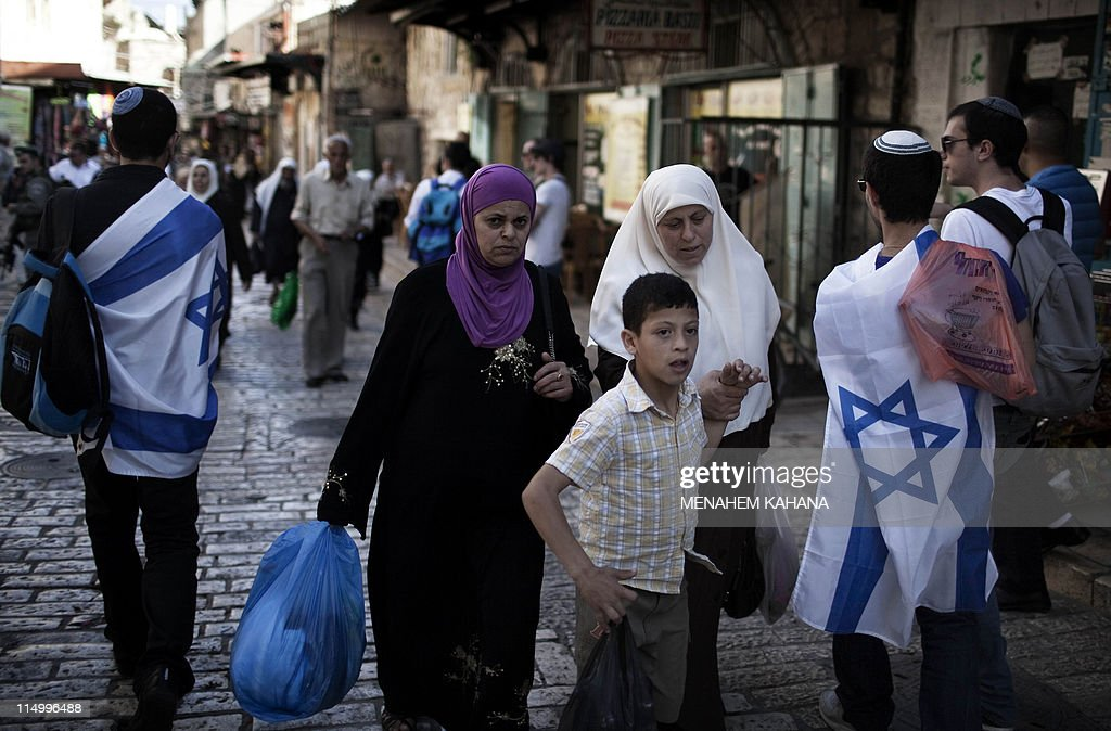 Palestinians walk past Israelis marching in the old city of Jerusalem on June 1 2011 during the Jerusalem Day parade in the city's mainly Arab...