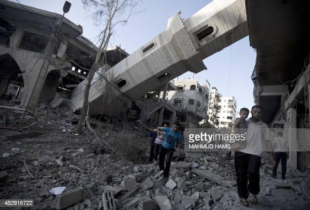 Palestinians walk past the collapsed minaret of a destroyed mosque in Gaza City on July 30 2014 after it was hit in an overnight Israeli strike...
