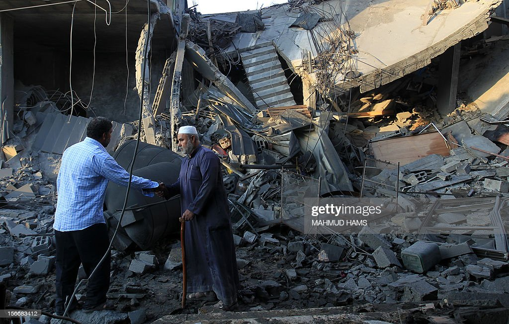 Palestinians walk past the debris of a destroyed home following an Israeli air strike in Gaza City, on November 19, 2012. Israeli air strikes on Sunday killed 31 Palestinians in the bloodiest day so far of its air campaign on the Gaza Strip, as diplomatic efforts to broker a truce intensified.