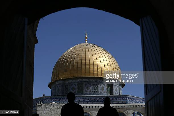 TOPSHOT Palestinians walk past the Dome of Rock at the AlAqsa Mosque compound before the Friday prayer in Jerusalem's Old City on October 14 2016 /...