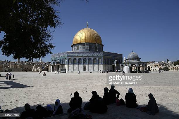 Palestinians walk past the Dome of Rock at the AlAqsa Mosque compound before the Friday prayer in Jerusalem's Old City on October 14 2016 / AFP /...