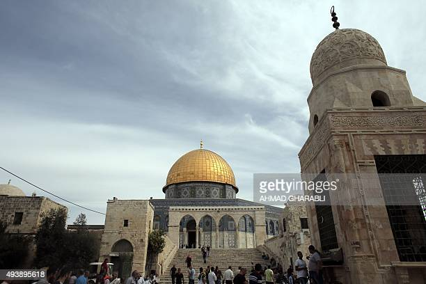 Palestinians walk past the Dome of the Rock at the AlAqsa Mosque compound in Jerusalem before the Friday prayer on October 23 2015 Earlier in the day...