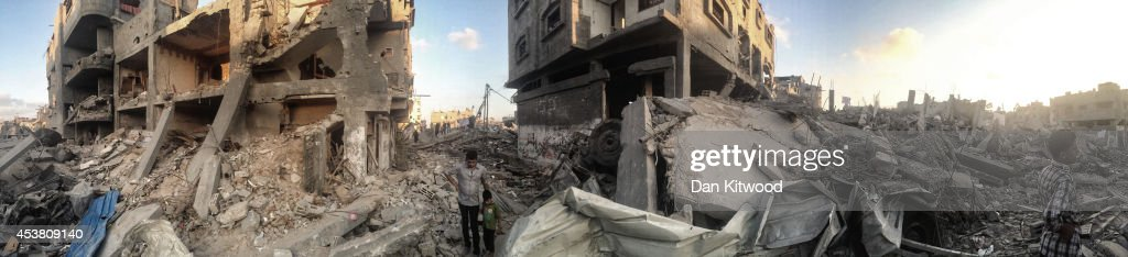 Palestinians walk through a destroyed area of housing on August 16 2014 in Gaza City Gaza A fiveday ceasefire between Palestinian factions and Israel...