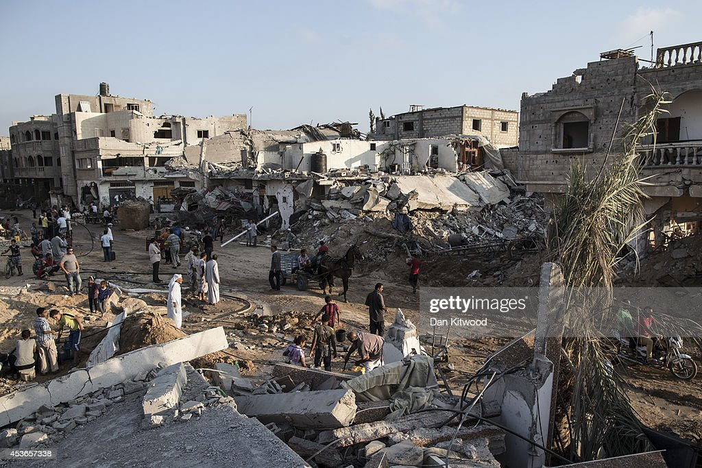 Palestinians walk through an area of destruction on August 15 2014 in Khuza'a Gaza A new fiveday ceasefire between Palestinian factions and Israel...