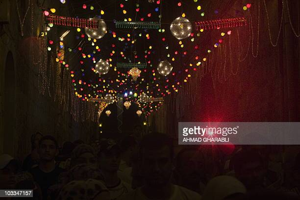 Palestinians walk under colored lights as they go to the first evening prayers at the alAqsa mosque in Jerusalem's Old City after breaking the fast...