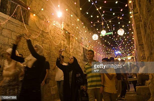 Palestinians walk under colored lights as they go to the first evening prayers at the alAqsa mosque at Jerusalem's old city Damascus Gate after...