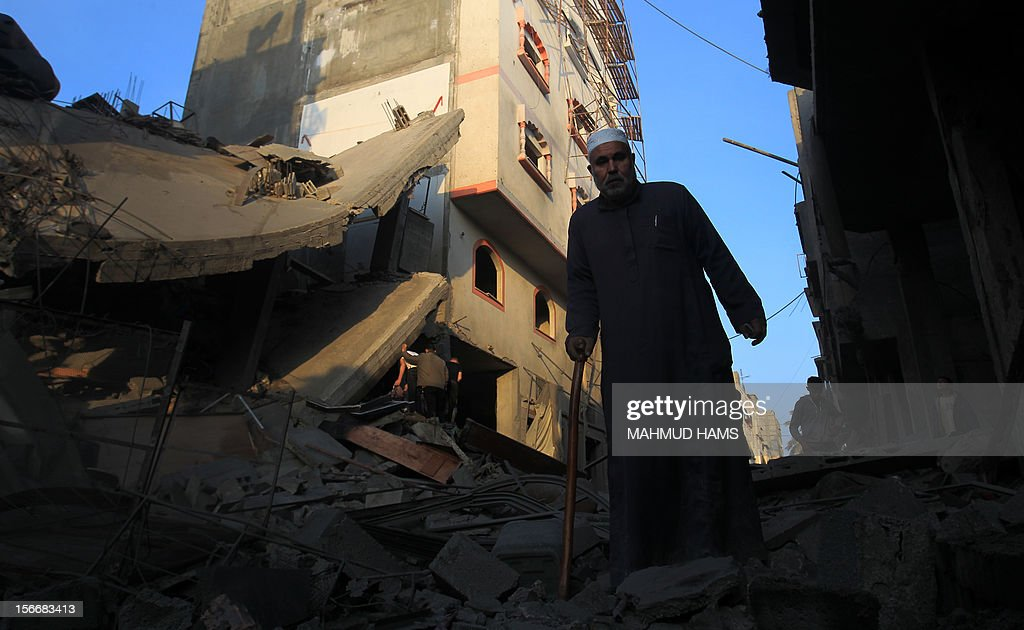 A Palestinians walks amongst the debris of destroyed homes following an Israeli air strike in Gaza City, on November 19, 2012. Israeli air strikes on Sunday killed 31 Palestinians in the bloodiest day so far of its air campaign on the Gaza Strip, as diplomatic efforts to broker a truce intensified. AFP PHOTO/MAHMUD HAMS