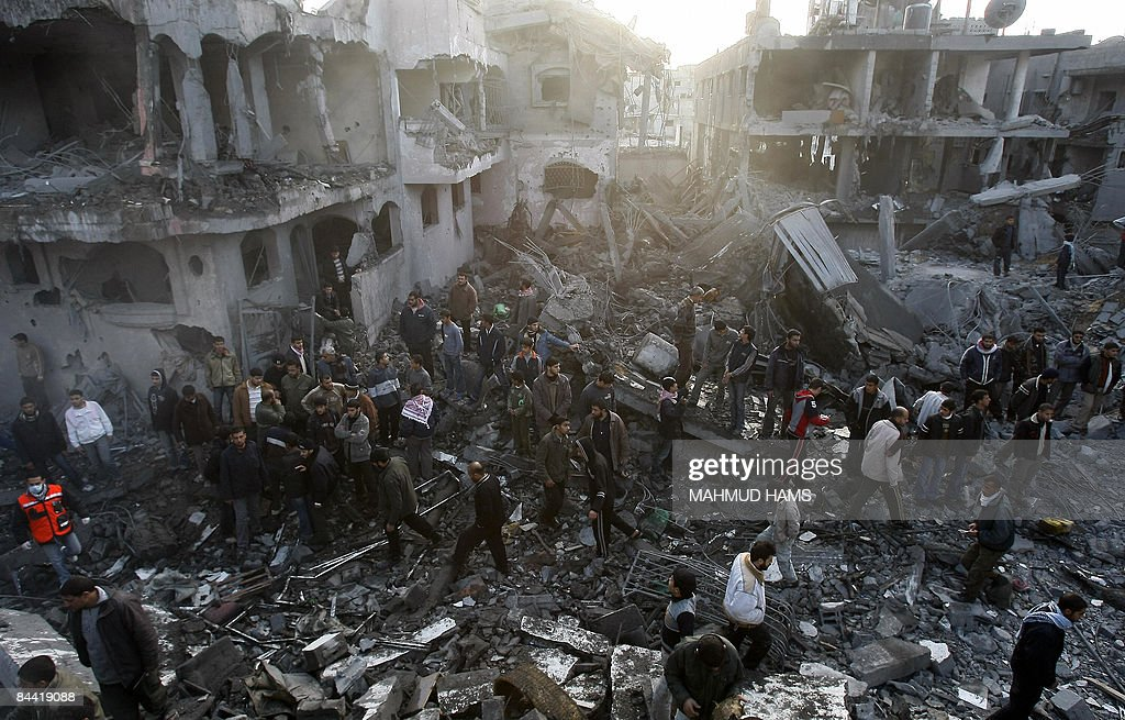Palestinians walks through the rubble to inspect the damage at the destroyed house of Hamas leader of Nizar Rayan following an Israeli air strike in Jabalia in the northern Gaza Strip on January 1, 2009. Rayan was killed today with his four wives and two of his children in an Israeli air strike in Gaza, medics said. Rayan, a hardliner within the Islamist group, was killed when a missile crashed into a five-storey house that he shared with his wives and children in Jabalia in the north of the territory, the medics said. AFP PHOTO/MAHMUD HAMS