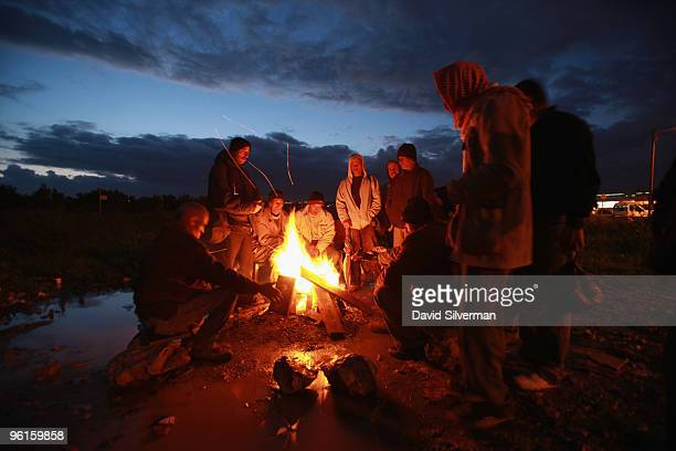 Palestinians warm themselves around a fire as West Bank labourers brave the cold weather while waiting to be picked up to work in the Jewish State on...