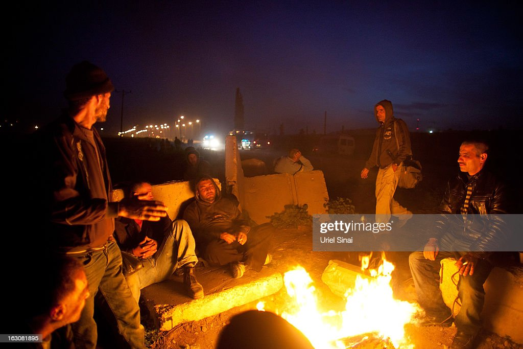 Palestinians warm up by a fire as they wait for a bus as a new line is made available by Israel to take Palestinian labourers from the Israeli army crossing of Eyal, near the West Bank town of Qalqilya, into the Israeli cities, on March 4, 2013. at Eyal crossing, West Bank. The new line service to ferry Palestinian workers from the West Bank to Israel, encouraging them to use it instead of traveling with Israeli settlers on a similar route.