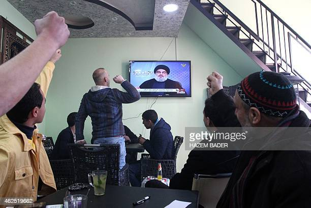 Palestinians watch Hassan Nasrallah the head of Lebanon's militant Shiite Muslim movement Hezbollah give a televised speech from an undisclosed...