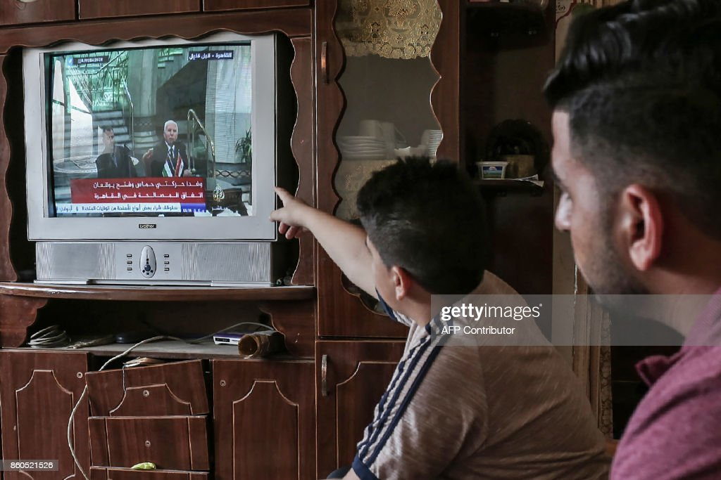 TOPSHOT - Palestinians watch on TV the signing of a reconciliation deal in Cairo between rival Palestinian factions Hamas and Fatah on October 12, 2017, in Rafah in the southern Gaza Strip. The new Hamas deputy leader and the head of Fatah's delegation struck the deal which was described by Palestinian Authority president Mahmud Abbas as a 'final agreement' to end their crippling division, which has at times erupted into deadly conflict over the past ten years. /