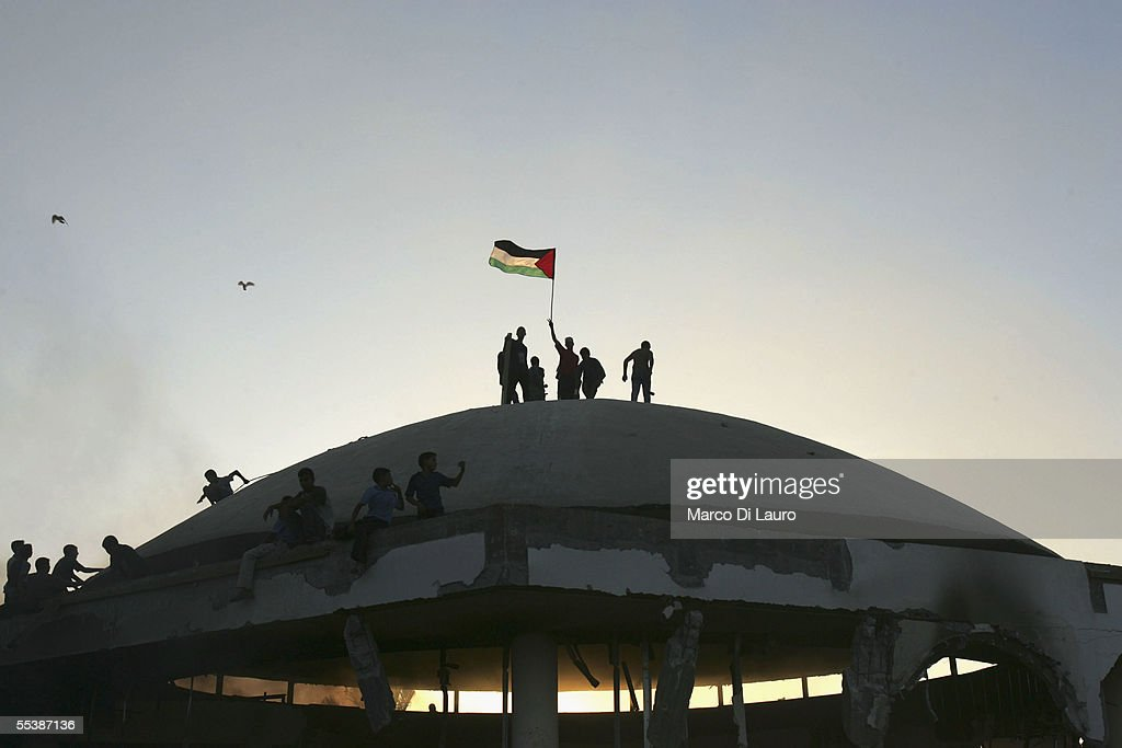Palestinians wave a flag as they stand on the roof of the demolished synagogue as they celebrate the Israeli withdrawal from the Netzarim Settlement...