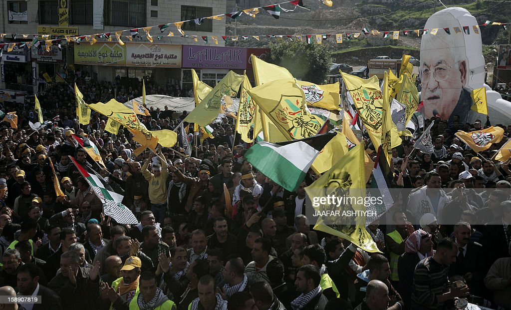 Palestinians wave Fatah movement flags and hold a large portrait of Palestinian president Mahmud Abbas (R) as they celebrate the 48th anniversary of the founding of the Gaza branch of the party during a ceremony in the West Bank city of Nablus on January 3, 2013. The anniversary commemorates the first operation against Israel claimed by its armed wing then known as Al-Assifa (The Thunderstorm in Arabic) on January 1, 1965. AFP PHOTO / JAAFAR AHTIYEH