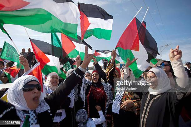 Palestinians wave flags during celebrations marking the prisoner swap deal reached between Israel and Hamas October 18 201 in the East Jerusalem...